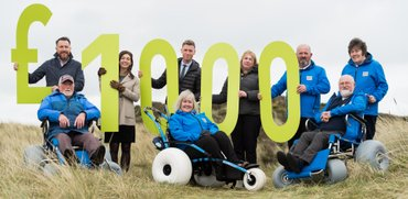 Vounteers holding £1000 sign in the sand dunes
