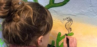 Close up of our artist painting the mural at The Bunker on Balmedie beach